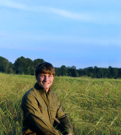 long sleeved: Young man kneels in a meadow near sunset   He is smiling happily and wearing jeans and olive long sleeved shirt