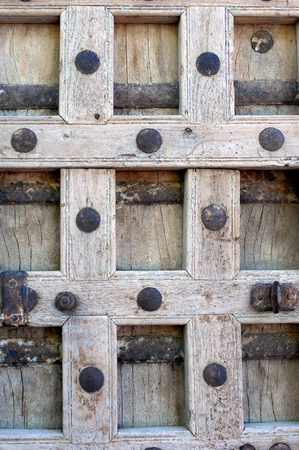 brads: Rustic and weathered, wooden door has rusty and time worn metal fittings.
