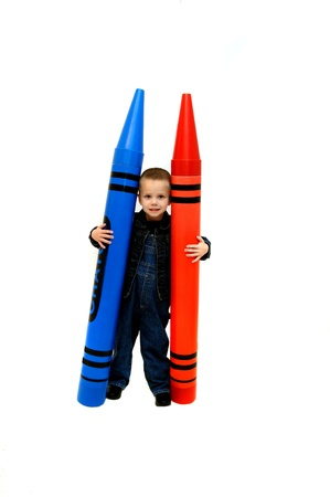 clutching: Small boy holds two giant crayons in red and blue   Crayons are bigger than he is   Studio setting with all white background with isolation