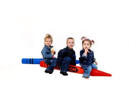 Three children sit on two giant colors in red and blue   They are dressed in denim jackets and jeans and are having a ball playing in an all white room  Stockfoto