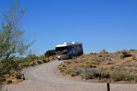 Big camper pulls into state park near Albuquerque, New Mexico.  Gravel road leads to camping spot. photo
