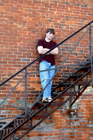 Young male leans against an old brick factory building   He is standing on the metal fire escape and is unsmiling and serious