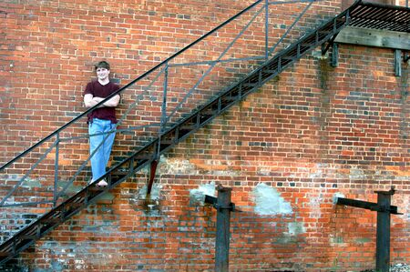 Young man leans against an old, derelict factory building   He is standing on a metal fire escape   Grunge jeans, barefoot and torn tee shirt  photo