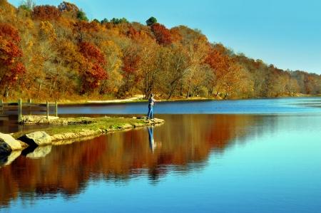 Lone visser werpt zijn lijn in klein meertje in het noorden van Arkansas Vroege ochtend licht reflecteert blauw in het meer