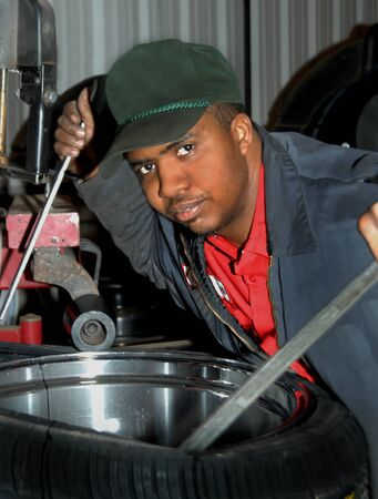 breaking down: African American man works on breaking down a problem tire at tire store   He is holding two tools and looking at camera  Stock Photo