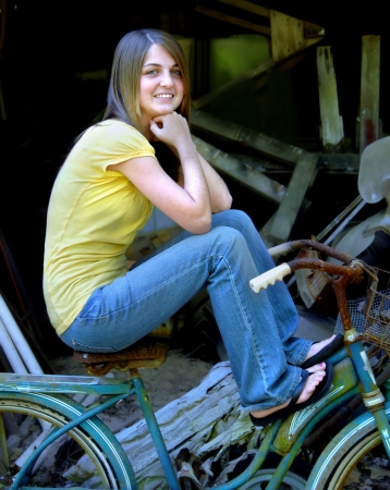 Young woman sits on an old bicyle in aqua and white   Junk surrounds her and she is smiling happily remembering events in her childhood