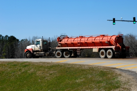 transporting: Eighteen wheeler tanker goes through green light   Orange tank with white cab  Stock Photo