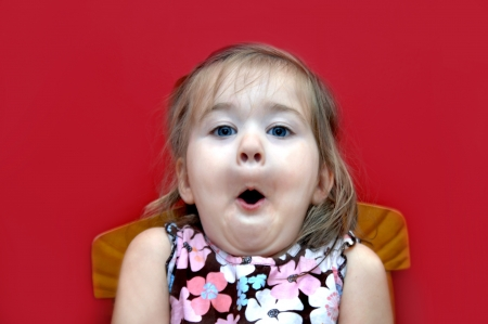Little girl sucks in her breath in surprise   She is sitting in a wooden chair against a red background Stock Photo - 15023838