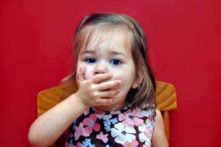 Little girl sits at the dinner table with her hand over her mouth   Vegetables and anything green makes her cover her mouth in distate   Bright red background