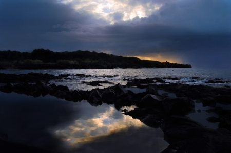 parting the sea: Rocky greeting for a new day is reflected in the ocean and shoreline pools on the Big Island of Hawaii at Whittington Beach Park   Rain clouds and pouring rain follow closely on its heels