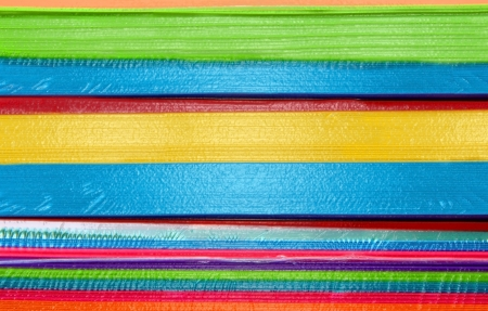 Stacks of papers in hot colors and brilliant hues are plastic coated and sit in reams ready for office use