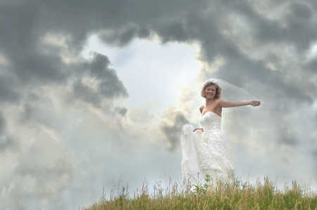Bride stands atop a hill with approaching storm clouds Sun breaks through with bride