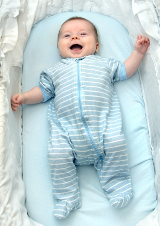 beaming: Beaming baby boy smiles his happiness   He is laying in a basinette on a blue cover