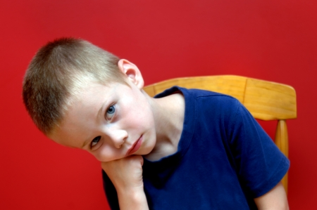 Little boy sits in wooden chair in front of a red wall   He leans his head in his hands and stares unsmiling   He is listless and dispondent  photo