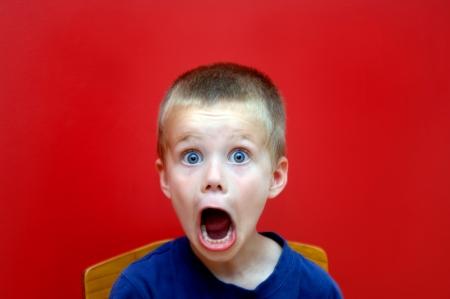 Kleine jongen zit in een houten stoel voor een heldere rode muur Zijn mond gapende is en zijn uitdrukking toont ontzet Verrassing en shock register in zijn expressie