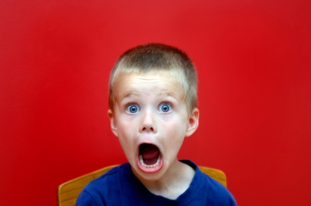 Little boy sits in wooden chair in front of a bright red wall   His mouth is gaping and his expression shows aghast   Surprise and shock register in his expression