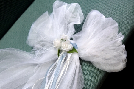 pew: Wedding bow of net, ribbon and beading lays on church pew waiting on the decorator