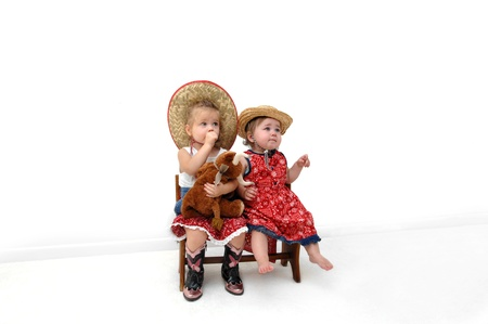 Big sister sits besides her little sister on a wooden bench   Both are dressed in western wear and hats   One is sucking her thumb and holding a stuffed bull toy  photo