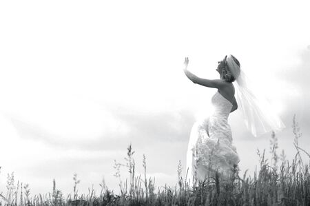 Bride embraces rays from heaven with outstretched hand She is standing on a hilltop with tall grass at her feet Her veil blows in the wind Black and white image