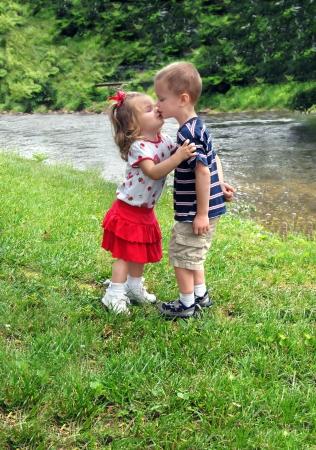 Broer en zus kus liefdevol Ze staan naast een kleine rivier genieten van een zonnige dag in de buitenlucht Stockfoto