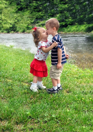 little boy and girl: Brother and sister kiss affectionately   They are standing besides a small river enjoying a sunny day outdoors