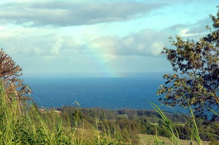showers: Rainbow ends in the ocean off the Hamakua Coast on the Big Island of Hawaii   Showers are still falling on the ocean Stock Photo