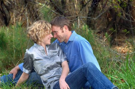 Attractive couple touch foreheads for a loving moment as they explore a wooded trail   They are sitting and resting with woods behind them  photo