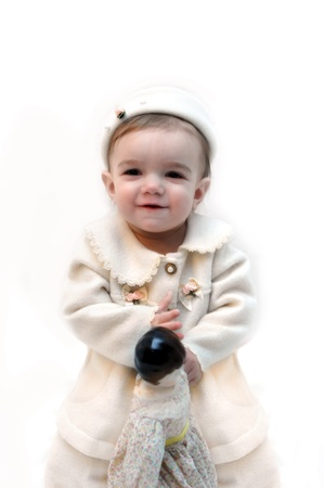 Sweet little baby is dressed in early 19th century outfit.  She is holding a porcelain doll and is smiling so sweetly.  Soft pink skin and off white outfit. photo