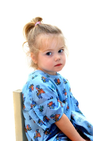apathetic: Little girl sits apathetic in blue print hospital gown.  She stares off into space as if dreaming of running and playing.