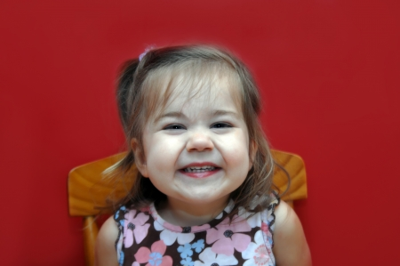 grins: Little girl sits in wooden chair against a bright red wall.  She grins an impish grin of pure joy. Stock Photo