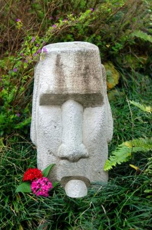 sacar la lengua: Stone faced tiki saca la lengua como un acto de rebeli�n. Esta cabeza de piedra cara finalmente ha tenido su raci�n de embobado turista. Foto de archivo
