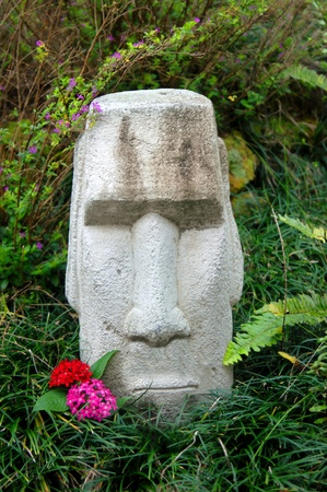 Stone faced tiki sits expressionless in a garden on the Big Island of Hawaii.  This stone faced head is decorated with red and hot pink flowers. photo