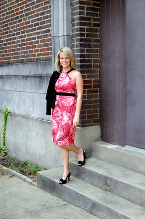 Young woman holds her jacket over her shoulder as she poses on the steps of the Old Rialto Cinema building in downtown El Dorado, Arkansas.  She is smiling and wearing a pink dress and black pumps. Stock Photo