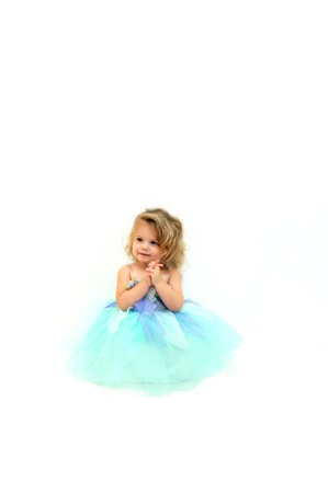 dressup: Beautiful little girl pretends to be a ballerina.  She is wearing a mint colored tutu and is clasping her hands in delight.  Blond curls spring freely around her face. Stock Photo