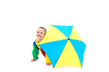 april showers: Little boy hides behind a colorful umbrella waiting for April showers to be over.  He is wearing a colorful raincoat and behind a yellow and blue umbrella. Stock Photo
