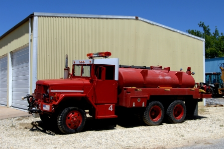 City fire truck is parked besides a storage facility.  Towanda, Kansas has a truck #4 painted red and white with siren and lights.