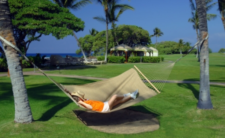 Older woman lays in a hammock slung between two palm trees on a resort on the Kohala Coast of the Big Island of Hawaii.  Her straw hat lays across her face and she is swinging to the rhythm of the trade winds. photo