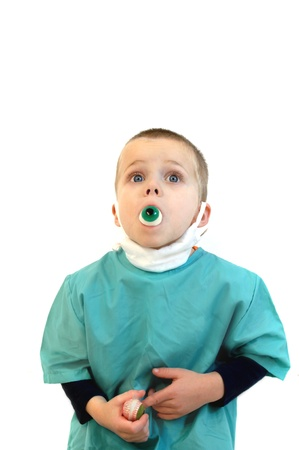 bugging: Little boy dressed in medical scrub and mask holds a candy eyeball in his mouth.  He is illustrating a metaphor for eye Popping.  He also is bugging his eyes. Stock Photo