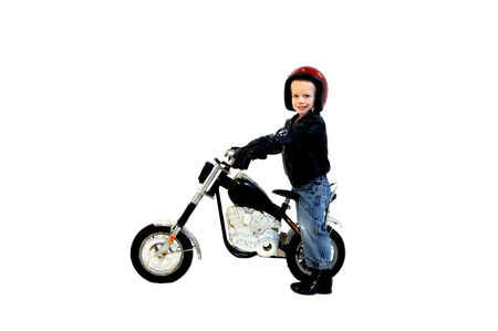 exhilarated: Little boy dreams big and his wish is to own and ride a big motorcycle.  He is riding a cycle with red helmet and smiling happily.  Anyone can dream and dream big.