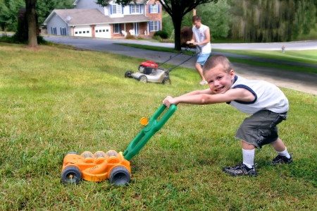 Small boy mows grass just like his dad.  He is grinning and pushing a toy lawn mower while dad mows with his.