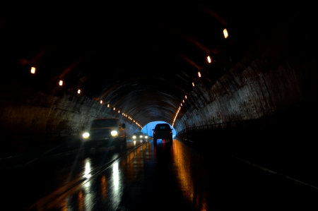 Tunnel traffic has added danger of wet roads.  Headlights throw rays of light in front of truck.