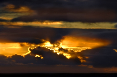 obscuring: Sunset is obscured by gathering stormy clouds.  This photograph could represent both darkness and light as the sun sets over Loupahoehoe Point on the Big Island of Hawaii. Stock Photo