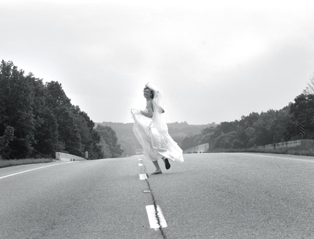 Bride laughs as she runs down a highway holding her gown.  Black and white photo. photo
