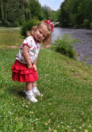 Little girl explores the banks of the Doe River in Tennessee   She is bent over looking down river    photo