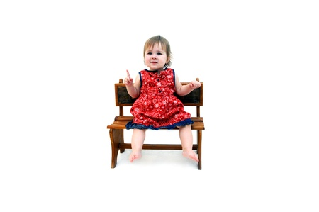 frowns: Little baby girl holds a single finger up to illustrate how old she is   Then frowns in confusion   She is wearing a red paisley print dress and is barefoot   All white room