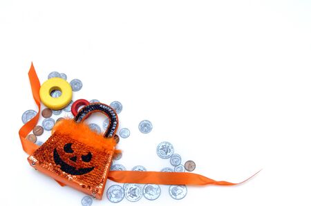 Halloween candy is expensive and adds up if you count in costumes, parties and transportation   Halloween purse and wooden candy lay across scattered coins Stock Photo - 15023772