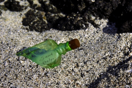 Green bottle has washed ashore and has a note inside it   Bottle also has water inside it   Rocky shore with tiny pebbled sand  photo