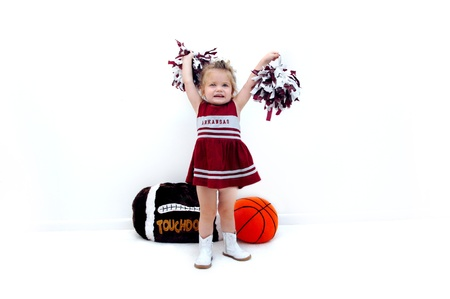 Little cheerleader dressed in burgundy and grey holds pom poms high in the air   She is wearing white gogo boots and standing in front of a stuffed football and basketball