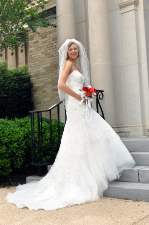 strapless: Bride anxiously begins her steps into the church   She is smiling happily as she begins her big day   She is holding a bouquet of red and orange silk roses  Stock Photo
