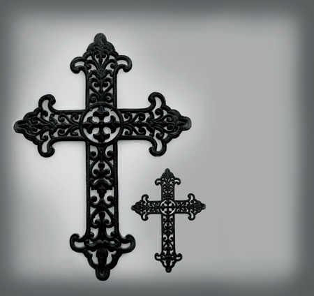 Rustic metal cross with scroll design hangs on a wedgewood green plaster wall   Darker tones frame edges